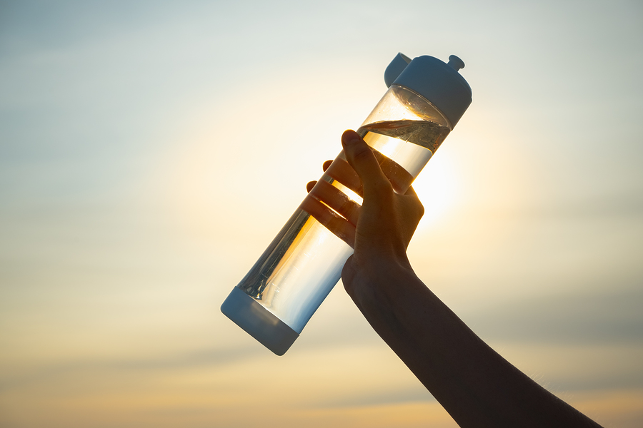 Human Hand Holds A Water Bottle Against The Setting Sun. UV-resistant plastic